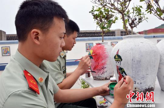 图为:边防官兵正在画卡通军人漫画。 赵志亮 摄