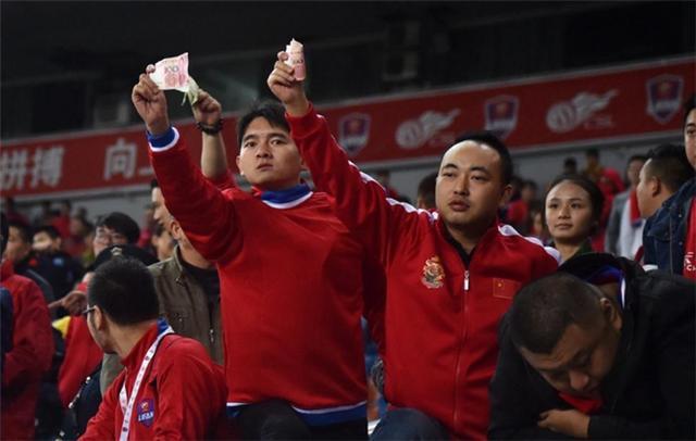 球队足协杯被淘汰 球迷看台掏百元钞票露诡异笑容