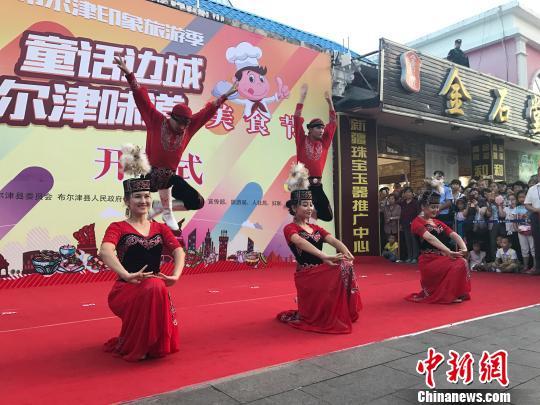"""在第二届""""童话边城布尔津味道""""美食节开幕式中,当地艺术团的青年们为观众带来一支哈萨克族舞蹈。 迪娜 摄"""