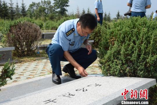 """93257部队部队长周忠耀和官兵们""""认领""""无名烈士墓,争当烈士""""后人""""。 杨毅 摄"""