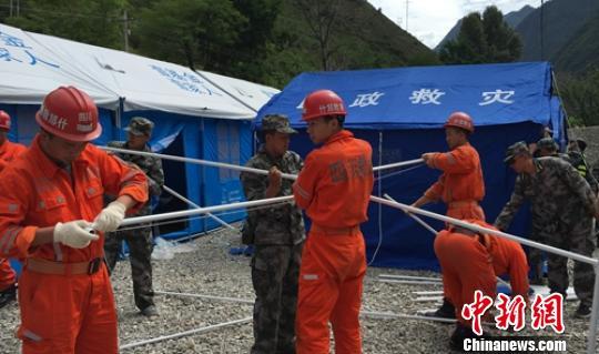 安全生产应急救援队救援人员震区帮助搭建安置帐篷。 四川安监 摄