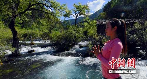 九寨沟姑娘娜美在树正群海景点练习瑜伽。安源 摄