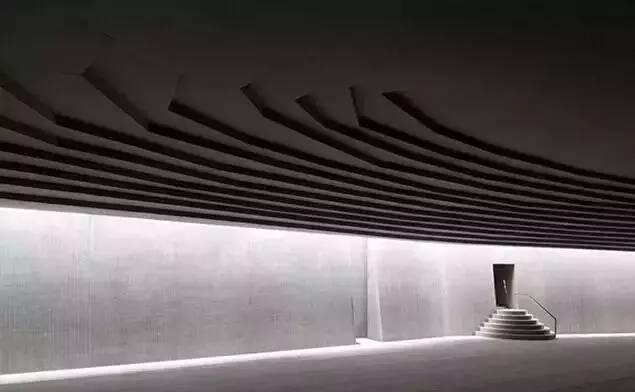 擦 光 在最近的十几年中,人们从光洗墙又发展出了一种新的灯光设计手法:擦光(Grazing light)。擦光与光洗最大的区别在于擦光更强调受光面材质本身的质感。而擦的方法,无非是将光源或者窄天窗安排在离受光面尽量近的地方,用最小的角度把光擦上去,利用平面本身的凹凸纹理制造出独特的光影效果。这个方法即便是对付很平整的墙面,例如抹平的水泥墙,也同样有效。用建筑评论常用的词语说,就是会产生丰富的戏剧性(drama)。 纽约Blue Fin餐馆中的擦光墙