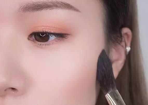 step7:用粉橘色的腮红涂抹在笑肌到颧骨的位置.图片