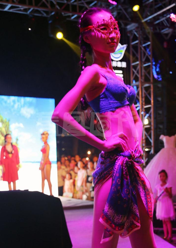模特们在红灯的照射下进行内衣秀和人体彩绘表演,更加