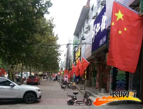 沿街商铺悬挂国旗。王尚武 摄
