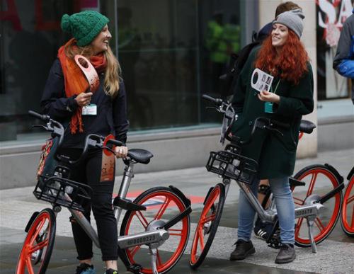 6月29日,在英国曼彻斯特,市民在体验摩拜单车。(图片来源:新华社)