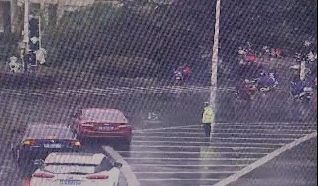 交警淋雨执勤全身湿透,路过车主减速扔来雨伞