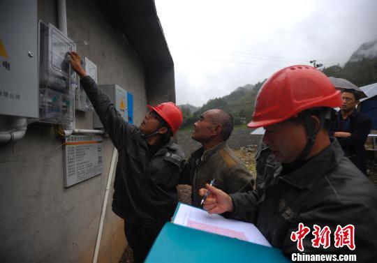 图为电力工人正在为村民检查电表和线路。 周毅 摄