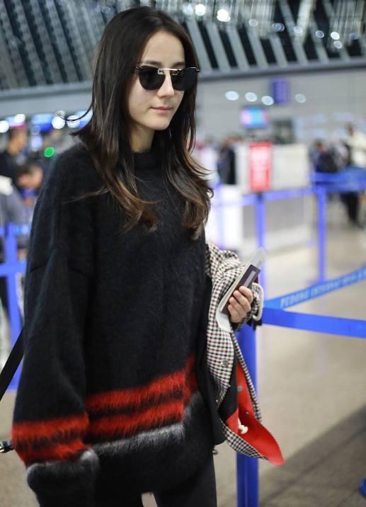 最近热巴现身机场,当天的她黑超遮面,一身黑红应季毛衣,简单又不失