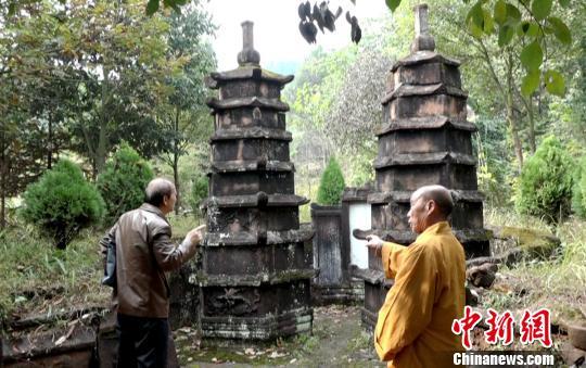 龙岩寺住持(右)向文史专家介绍双子墓塔。 徐志雄摄