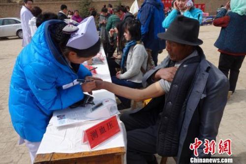 资料图:医疗志愿服务队对当地群众测量血压。 孙睿摄