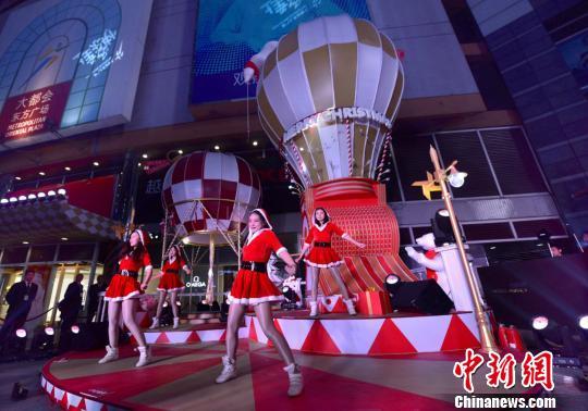 """随着圣诞节的临近,重庆市中心的商业中心也相继进入""""圣诞模式""""。图为重庆市中心的大都会东方广场外场的圣诞热气球。 钟欣 摄"""