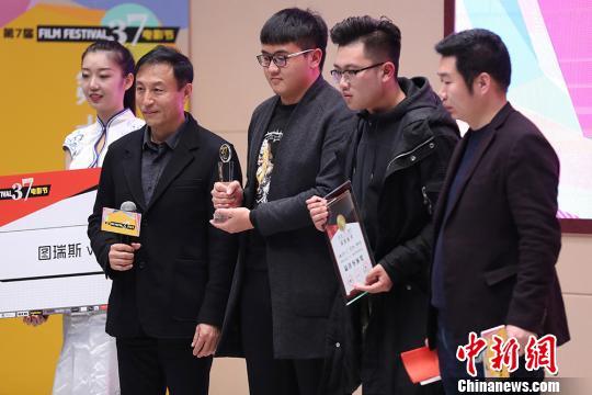 王洛勇(左二)为获奖者颁奖。 泱波 摄