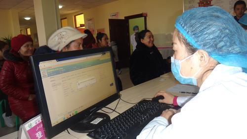 11月30日,在喀什市第一体检中心,检录台的医务人员正在给群众办理体检指引单。记者张治立摄