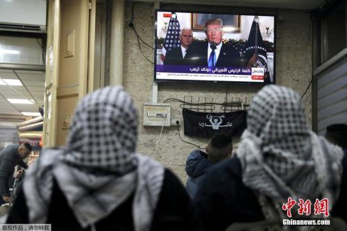图为巴勒斯坦民众在耶路撒冷旧城区观看特朗普发表公告的直播画面。