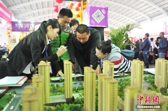 资料图:辽宁省沈阳市,春季房交会现场,销售人员在给市民讲解。孙昊声摄