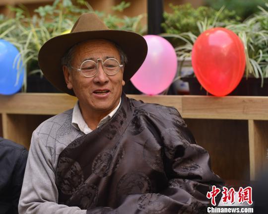 """70多岁的公布旺扎是西藏图书馆的""""常客""""。图为公布旺扎在活动中,向馆方""""建言献策""""。 周文元 摄"""