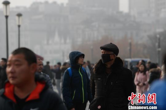 跨年日上海遭遇空气重度污染,外滩风貌区仍吸引不少游客前来游玩。 张亨伟 摄