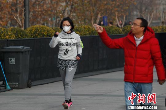 上海市民戴口罩在外滩观景平台上晨跑。 张亨伟 摄