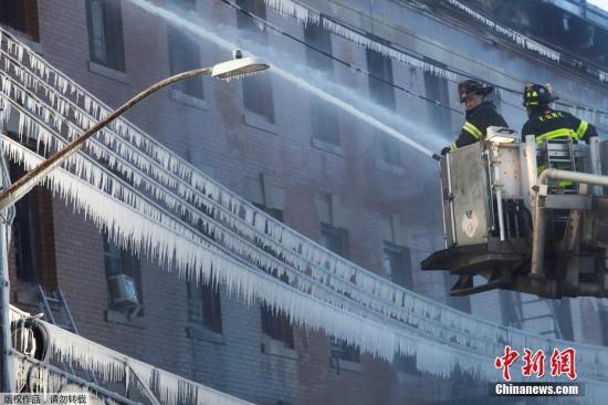 当地时间2018年1月2日,美国纽约,消防员对抗布朗克斯区的大火。火灾发生在寒冷的凌晨,据报道多人受伤,超过200名消防队员投入灭火。