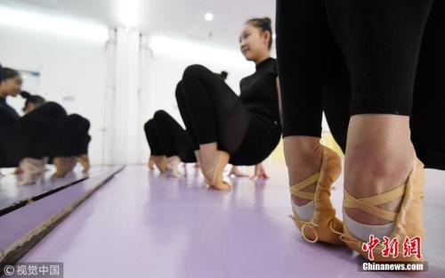资料图:舞蹈专业艺术生在练功房练习站脚背。郝群英摄图片来源:视觉中国
