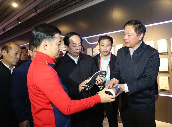 安踏集团董事局主席丁世忠向国家体育总局领导介绍安踏最新科技产品