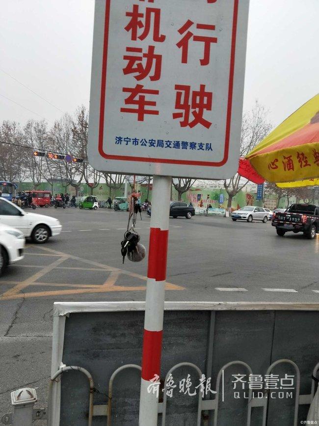 """""""当时我在路口等红绿灯,看一串钥匙挂在指示牌上面很是醒目,从交通协管员那里了解到,是早上有市民急匆匆上班不小心在路口掉下的,她就捡了起来挂在路口显眼的地方,失主回来找的话一眼就能看到.图片"""