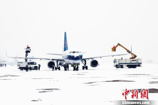 南航机务人员正在为一架即将起飞的飞机进行除冰作业。 时晨摄