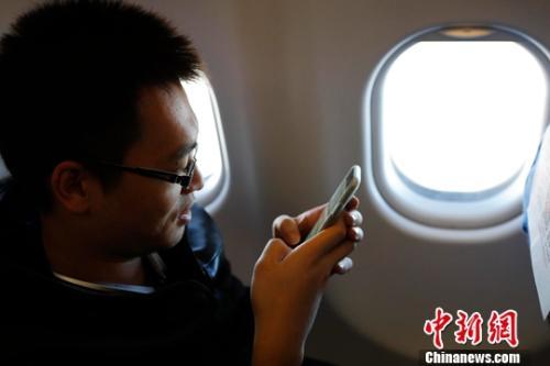 资料图:在东航MU5137航班上,旅客全程在飞行模式下可以使用手机。殷立勤摄