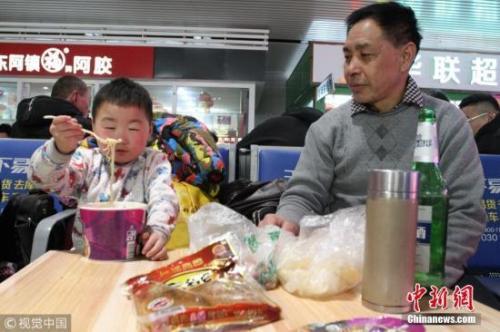 资料图:春运途中,有旅客喝着小酒就花生。图片来源:视觉中国
