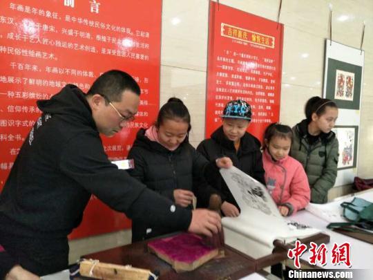 武强年画博物馆工艺师指导观众动手做木版年画。 陈贺芝 摄