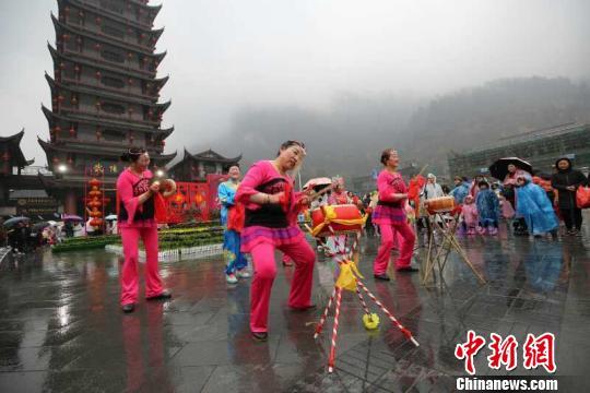 武陵源社区居民为冒雨为游客表演节目。 吴勇兵 摄