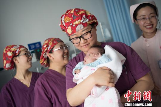 山西省儿童医院新生儿重症病房内,医护人员轮流抱起明天即将出院的小涛。 韦亮摄