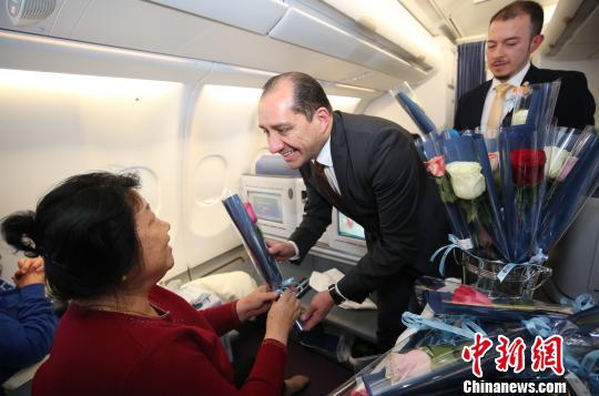 厄瓜多尔外交官在南航飞机向女性乘客赠送厄瓜多尔玫瑰 马旭辉 摄