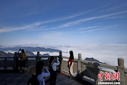 游客在蓝天云海中留影。 刘金文 摄