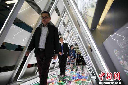 """""""京港中学生地铁列车模型创意科技大赛""""在北京启动。图为嘉宾们走进启动仪式现场搭建的一个三角形""""隧道"""",其内设3D全息投影,地面上的轨道会随着乘客行进的步伐幻化出绿植、鲜花,表达美好寓意。 张宇亮 摄"""