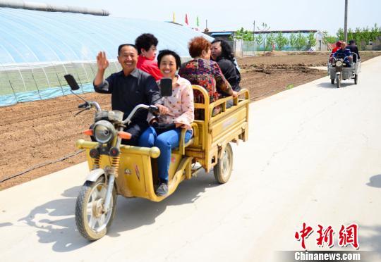 图为在东阿县草莓采摘基地里,村民们用三轮车拉着前来观光采摘的游客。 秋歌 摄