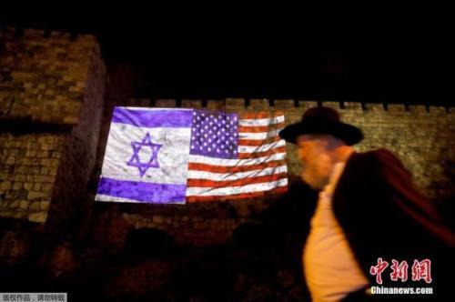 图为在耶路撒冷旧城区的一面墙上,以色列国旗和美国国旗被接在了一起。