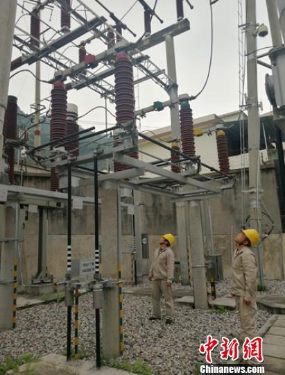 电力员工正在变电站排查设备。 钟欣 摄