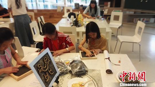 在史家小學,泰國學生與中國學生一同用黏土製作中外文字。 王婧 攝