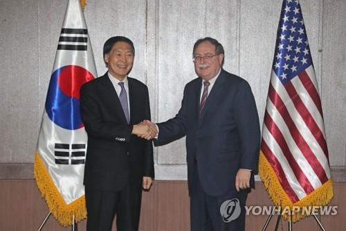 资料图片:4月11日上午,韩美第10次防卫费分担第二轮谈判在济州国际和平中心启动。会议前,韩方代表张元三(左)与美方代表蒂莫西・贝茨握手。(图片来源:韩联社)