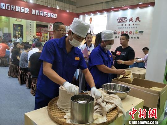 东莞国际茶业博览会1日在广东东莞开幕。图为展览现场演示古法制作普洱茶饼 李纯 摄