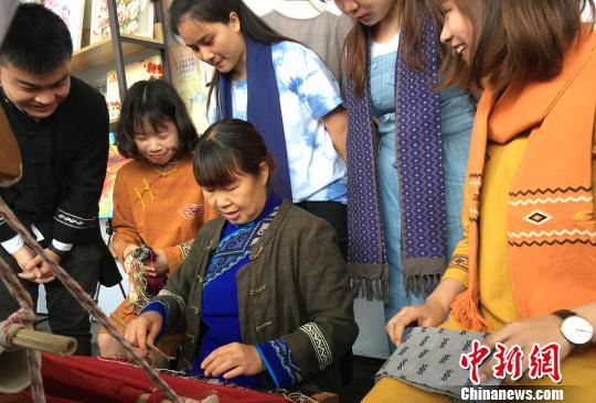 土家织锦传承人叶英(中)在演示该项目的挑花环节。 向一鹏 摄