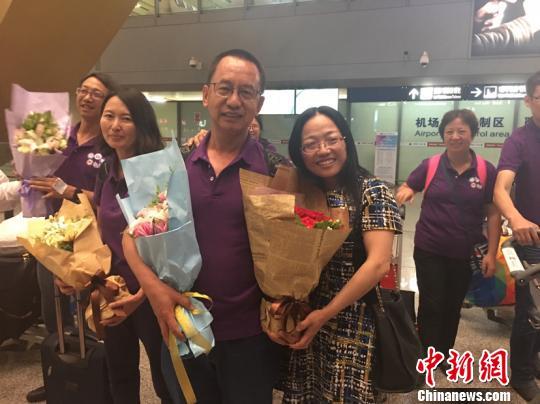 图为李武在机场收到妻子送的玫瑰花 陈静 摄