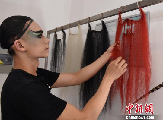 图为演出开始前,演员在后台化妆间整理道具。 周毅 摄