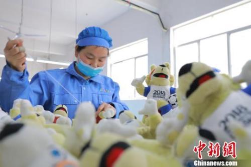 在工厂车间,工人完成最后一批吉祥物的缝制。供图