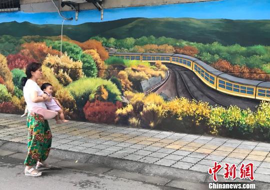 喜爱手绘墙的婆孙俩。 徐杨�t 摄