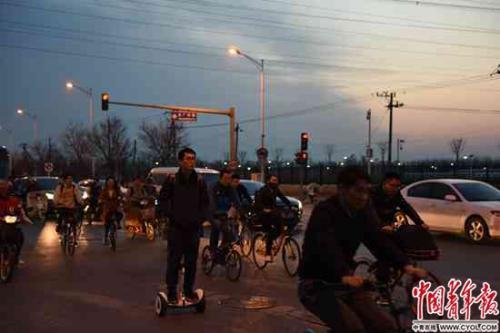 后厂村路路口,一名男子踩着电动平衡车过马路。据说这里以名字土和堵车闻名。实习生 杨子怡 摄