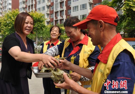 图为社区工作人员将煮熟的粽子送给环卫工人。 苑立伟 摄